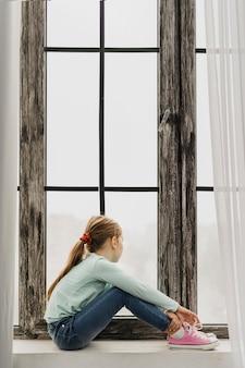 Bambina seduta sul davanzale di una finestra
