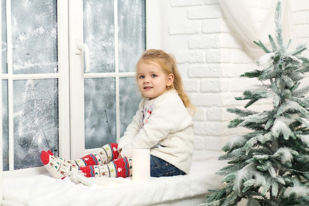 Little girl sitting on the windowsill in the evening before christmas