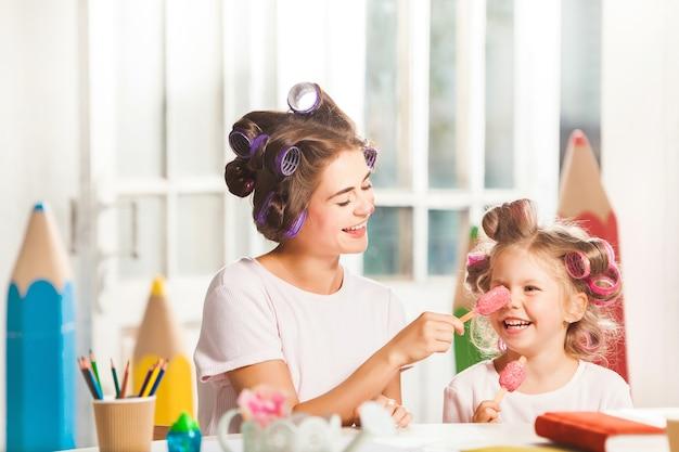 그녀의 어머니와 함께 앉아서 아이스크림을 먹는 어린 소녀