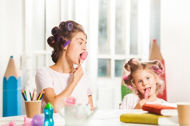 Маленькая девочка сидит с матерью и ест мороженое