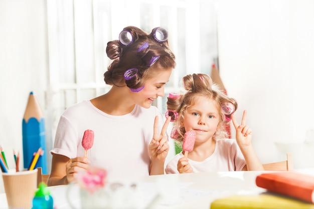 어린 소녀 그녀의 어머니와 함께 앉아서 아이스크림을 먹고