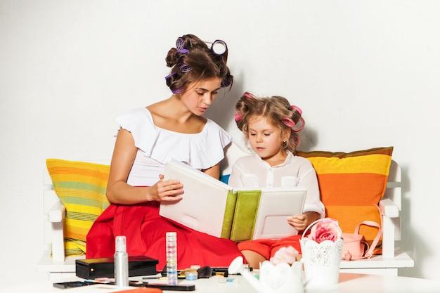 彼女の母親と一緒に座っているとフォトアルバムを見て少女