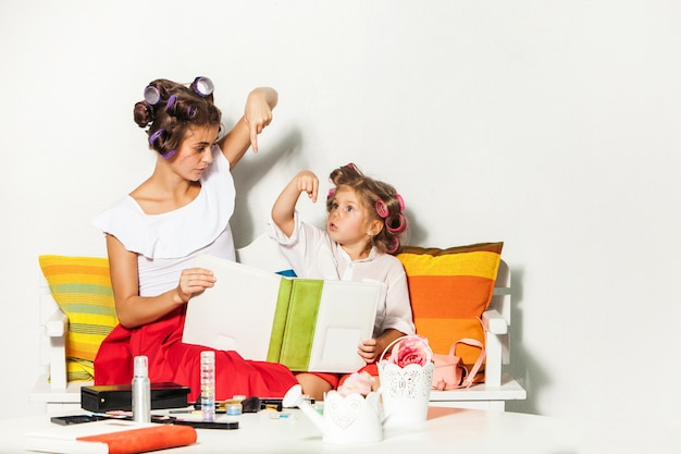 Маленькая девочка сидит со своей матерью и смотрит фотоальбом
