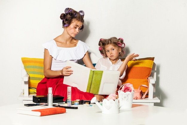 Маленькая девочка сидит с матерью и смотрит фотоальбом