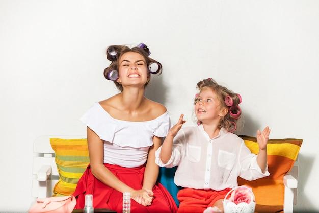 어린 소녀 그녀의 어머니와 함께 앉아서 연주
