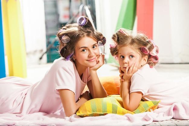 彼女の母親と一緒に座っていると遊ぶ少女