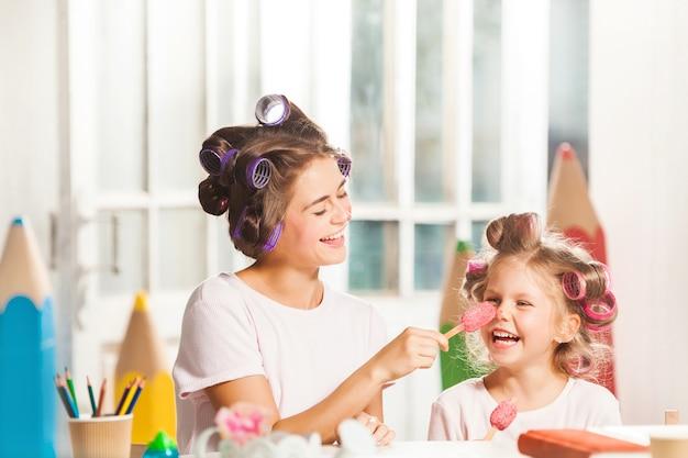 Bambina seduta con sua madre e mangiare il gelato