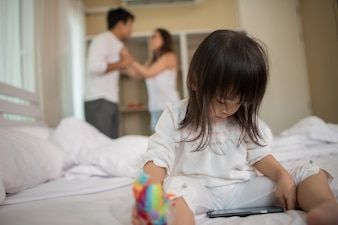 Little Girl sitting with her parents on the bed looking serious