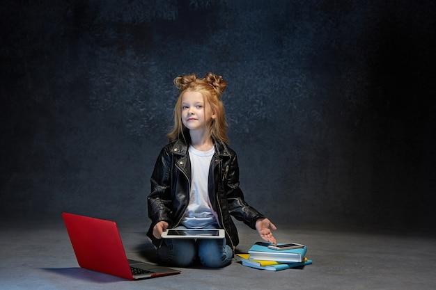 ノートパソコン、タブレット、灰色のスタジオで電話で座っている小さな女の子