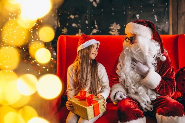 Маленькая девочка сидит с санта и подарки на рождество