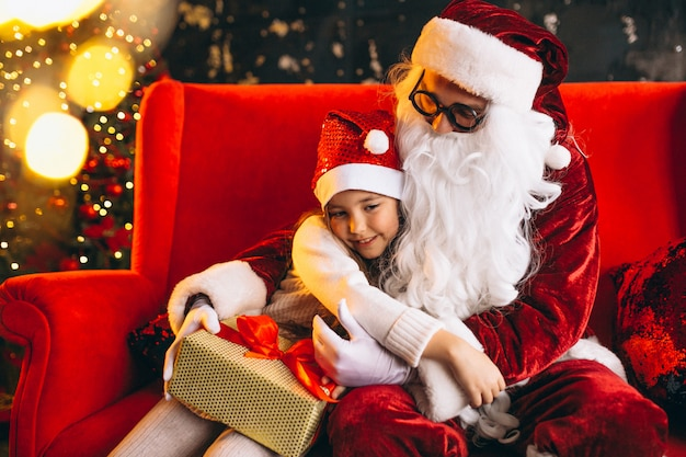 Little girl sitting with santa and presents on christmas
