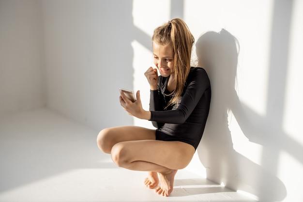 体操のクラスでスマートフォンと一緒に座っている少女