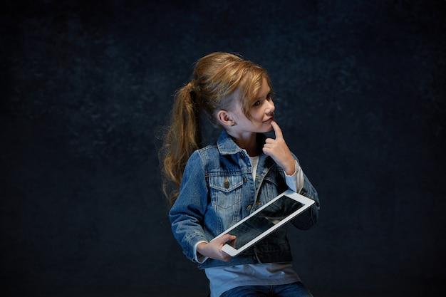タブレットで座っている小さな女の子