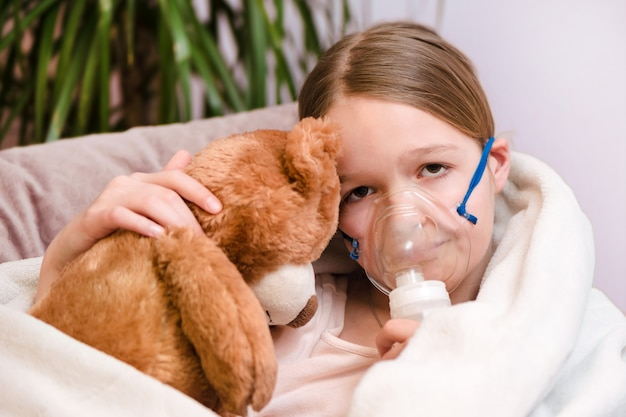 Little girl sitting with a toy on the couch in a mask for inhalations, making inhalation with nebulizer at home inhaler.