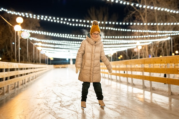 Little girl skating on ice rink outdoors in the park