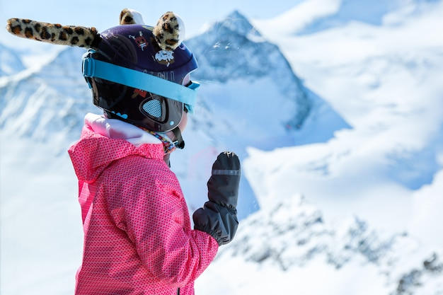Little girl in ski helmet looks at the mountains through the glass in the austrias highest coffee house at mountain peak in tirol, pitztal glacier
