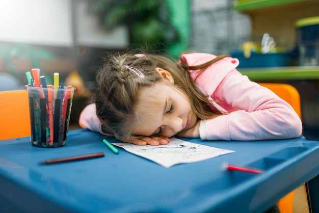 Little girl sleep in play area after drawing, pet shop. tired kid in petshop, goods for customers and domestic animals