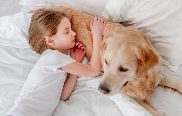 어린 소녀 자고 침대에서 골든 리트리버 강아지를 포옹. 아침 시간에 애완 동물과 함께 낮잠을 자고있는 아이. 집에서 소유자와 강아지