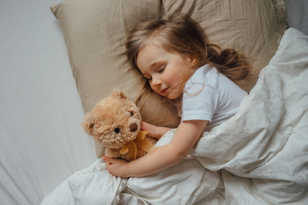 Little girl sleeping in bed embracing soft toy at home, top view