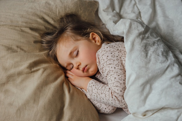 Little girl sleeping in bed at home, top view