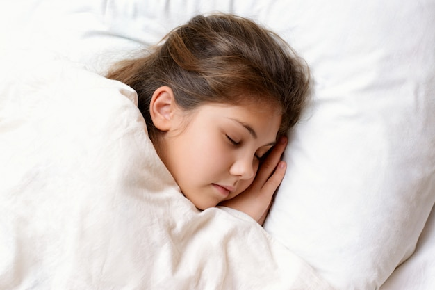 Little girl sleeping on comfortable pillow in bed