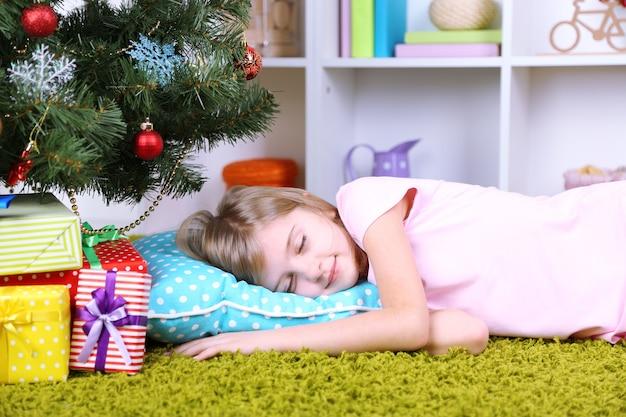 방에 있는 크리스마스 트리 근처에서 자고 있는 어린 소녀