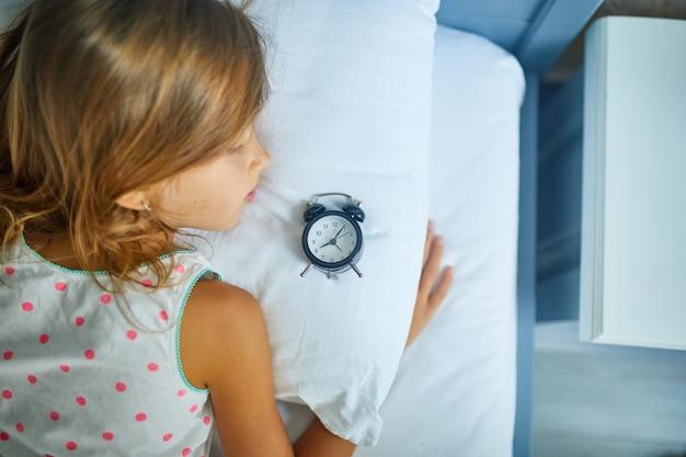 오후에 집에서 크고 아늑한 흰색 린넨 침대에서 자고 있는 어린 소녀