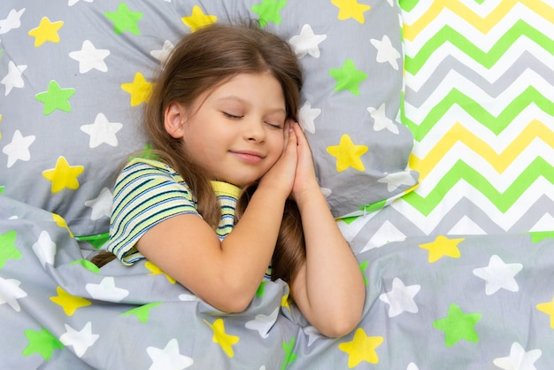 A little girl sleeps in bed with a sweet sleep at night.