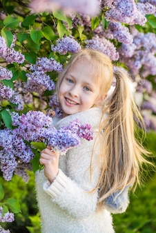 Little girl smelling lilac flowers in sunny day.