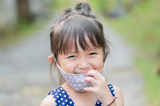 Маленькая девочка улыбка имеет защитную маску из ткани