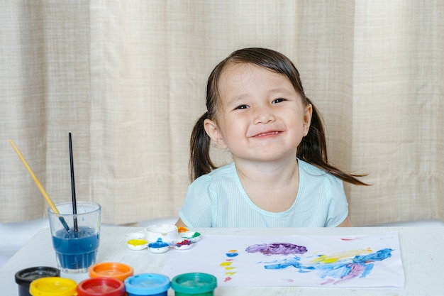 Little girl smile painting with paintbrush and colorful paints children development concep