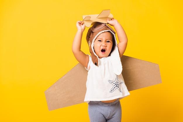 Маленькая девочка улыбается в шляпе пилота и в очках с игрушечными крыльями из картона.
