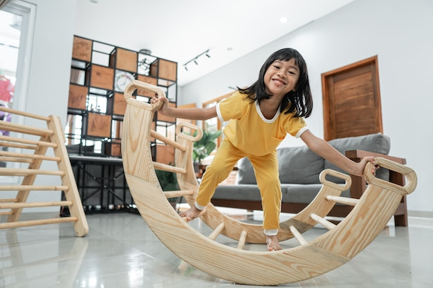 Little girl smile while playing balance in pikler triangle toy at home