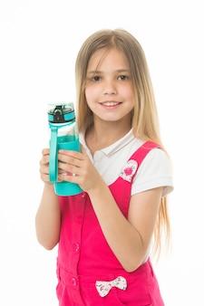 Улыбка маленькой девочки с пластиковой бутылкой, изолированной на белом. счастливый ребенок в розовом комбинезоне держит бутылку с водой. питьевая вода для здоровья. жажда и обезвоживание. детская активность и энергия.