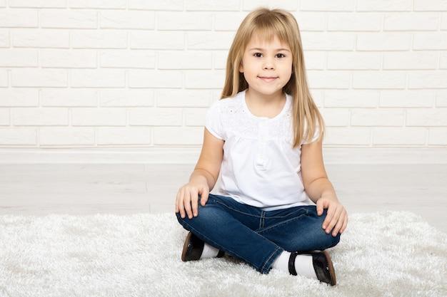 Маленькая девочка улыбается и сидит на полу в комнате