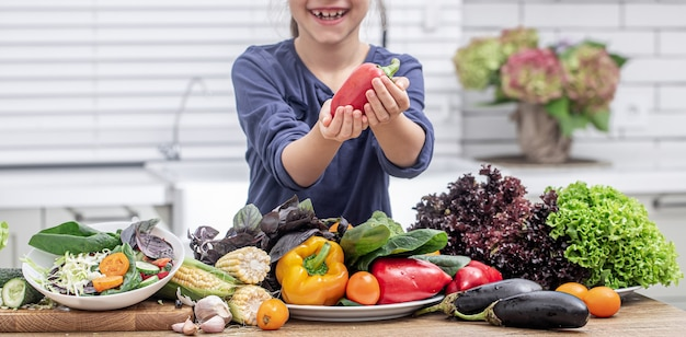 Little girl smiles and holds bell pepper in her hand while preparing salad on blurred background.