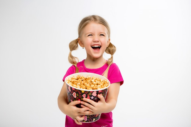 Little girl smiles with a bucket of popcorn