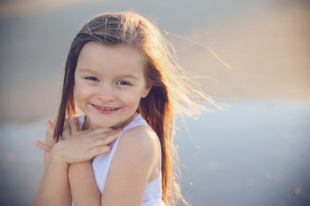 웃 고 사랑 제스처를 보여주는 어린 소녀
