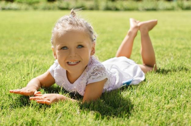하얀 드레스를 입고 잔디에 누워있는 동안 훌륭하게 웃는 어린 소녀.