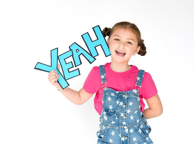 Little girl smiling happiness holding comic word yeah portrait