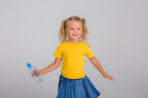 Little girl smiling holding bottle of water