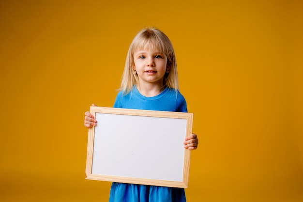 Little girl smiling holding an empty drawing board, space for text