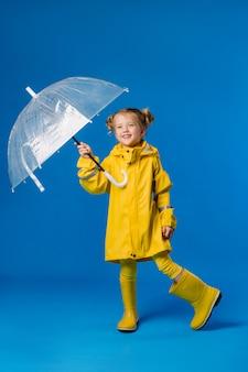 우산을 들고 노란 우비와 고무 장화에 웃는 소녀