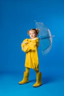 黄色いレインコートと傘を保持しているゴム長靴に笑みを浮かべて少女