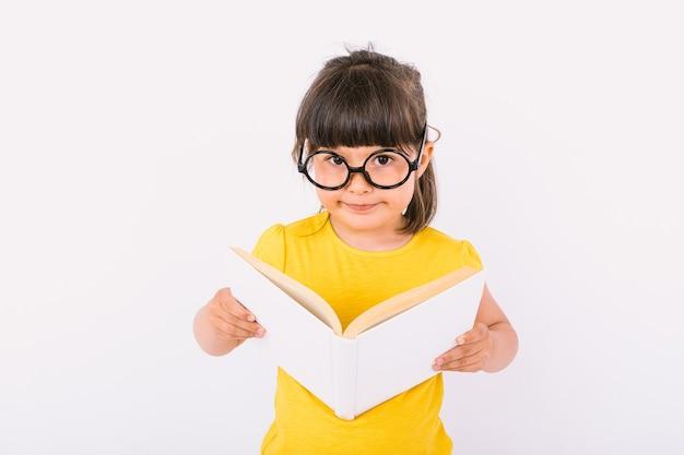 Маленькая девочка улыбается, в желтой футболке и круглых черных очках, держит в руках открытую книгу и смотрит в камеру на белом фоне