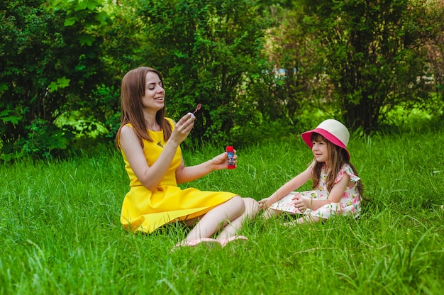 Little girl smiling while her mother blows soap bubbles