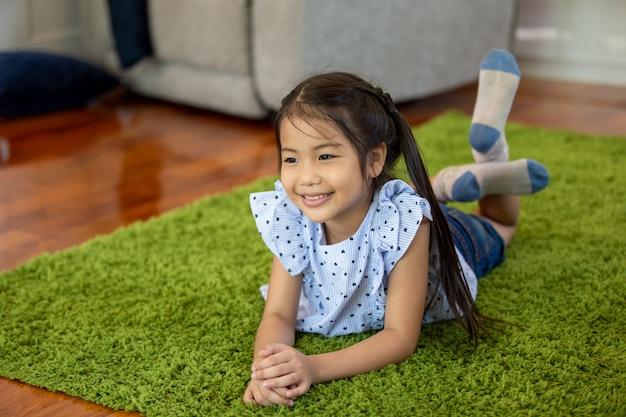 Little girl smiling while lying on carpet