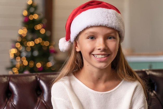 Little girl smiling while wearing a santa's cap