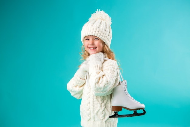 Little girl smiling in a winter white hat and sweater, holding skates