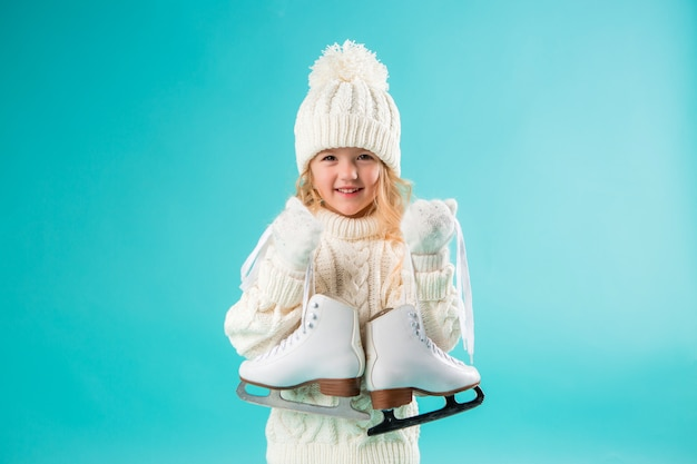 Little girl smiling in a winter white hat and sweater